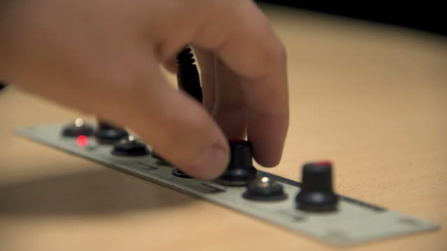 a hand plugging the jack of an earphone into a studio of a radio station and regulating the volume - cavo d'acciaio video stock e b–roll