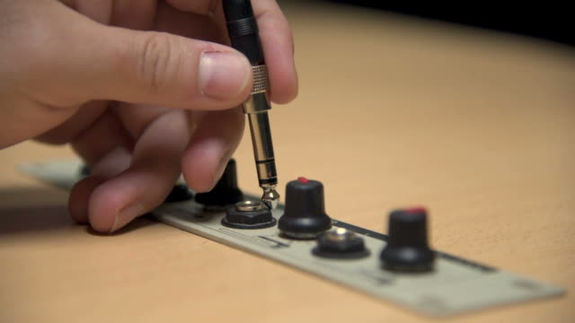 a hand plugging the jack of an earphone into a studio of a radio station - cavo d'acciaio video stock e b–roll