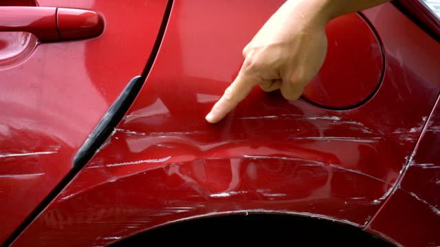 vidéos et rushes de main point à rayé de peau de peinture du véhicule. - endommagé