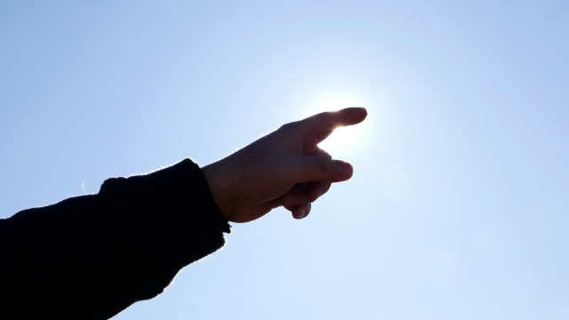 Hand pointing to sun in backlight. Male finger with optimistic gesture video