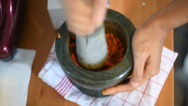 Hand Pounding turmeric Spice in Stone Mortar. Hand Pounding turmeric Spice in Stone Mortar. grind stock videos & royalty-free footage