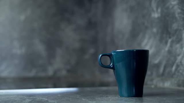 濃い青色のマグカップにコーヒーを注ぎ、ミルクを入れ、スプーンでかき混ぜる - キッチンカウンター点の映像素材/bロール