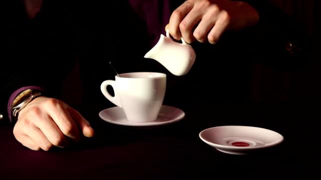 hand gießen eis auf eine tasse kaffee - milchkrug stock-videos und b-roll-filmmaterial