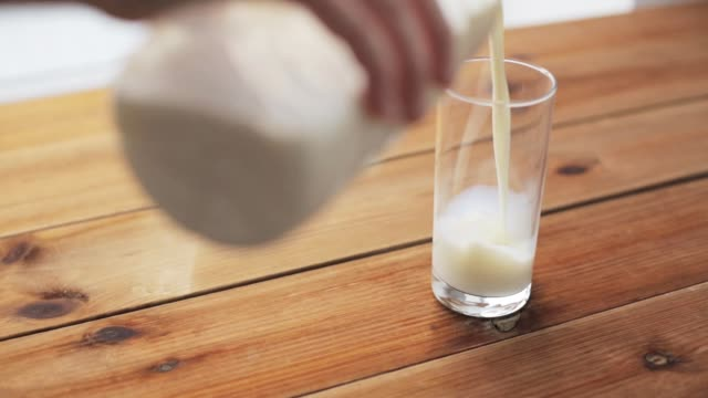 vídeos y material grabado en eventos de stock de verter la leche a mano en vidrio sobre mesa de madera - leche
