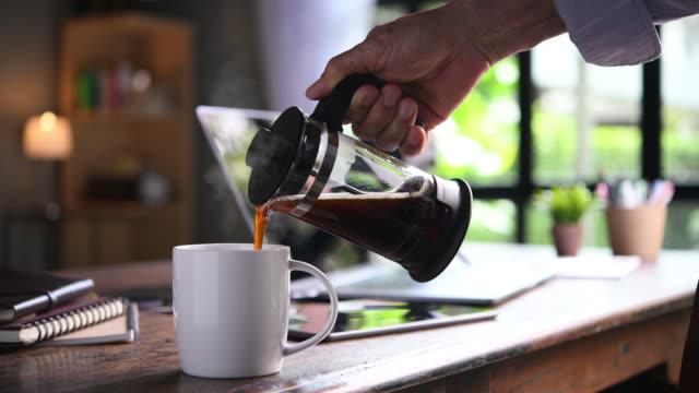 vidéos et rushes de une main versant le café fumant dedans à une tasse sur un bureau de travail quand travail de la maison - pots de bureau