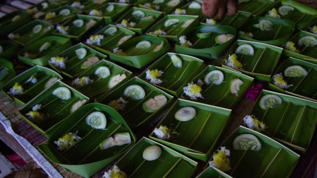 hand prepares hindu offerings with palm leaves, flowers, and vegetables Bali