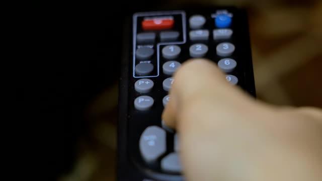 Hand presses remote control a close-up video