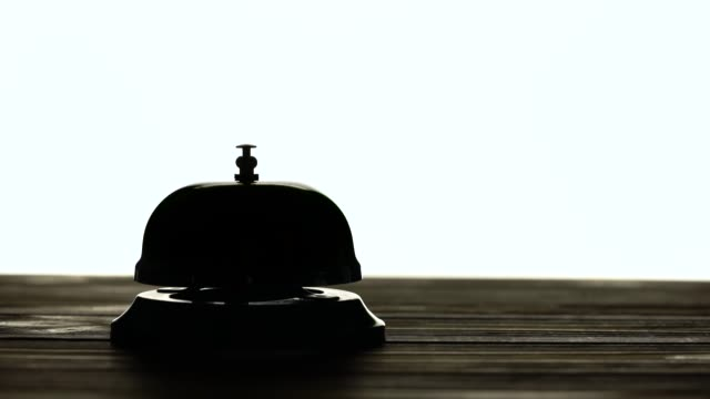 Hand presses the bell at the reception. White background. Silhouette video