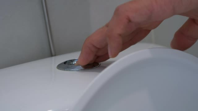 Hand pressing the button of a white ceramic toilet bowl Close up,Hand pressing the button of a white ceramic toilet bowl water wastage stock videos & royalty-free footage