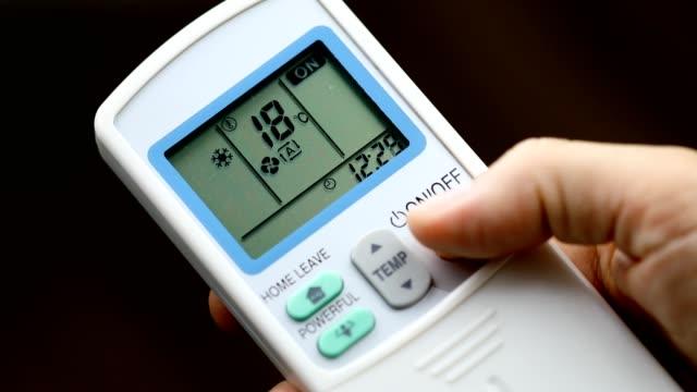 手はエアコンを起動するには、リモートコントロールのボタンをオンに押すと、部屋を冷やします - エアコン点の映像素材/bロール