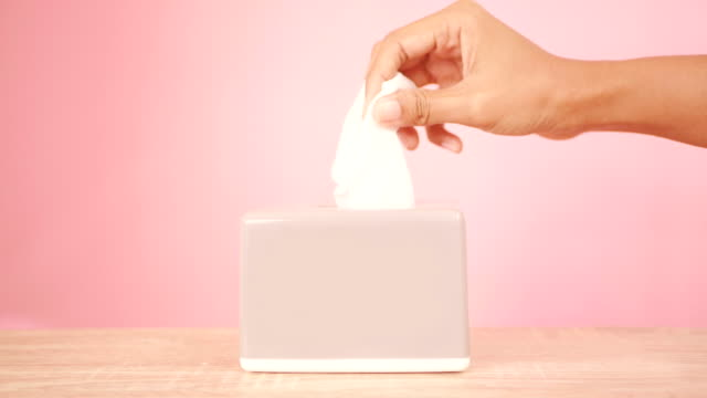 vídeos de stock e filmes b-roll de hand pull off face tissue paper from the grey box 3 times on pink background , hygine concept , 4k dci resolution - puxar