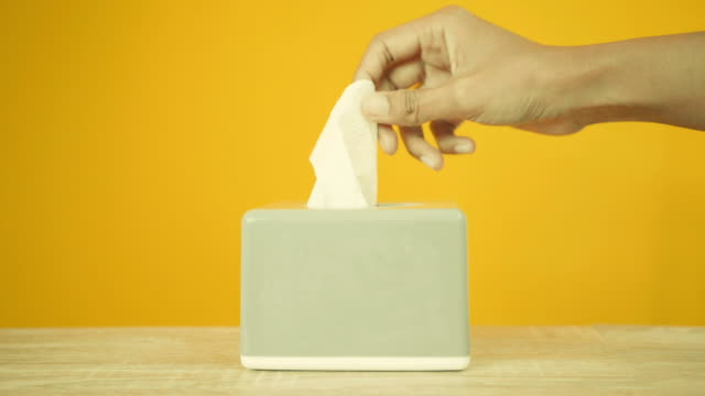 Hand pull off face tissue paper from the grey box 3 times on yellow background , hygine concept , 4k Dci resolution