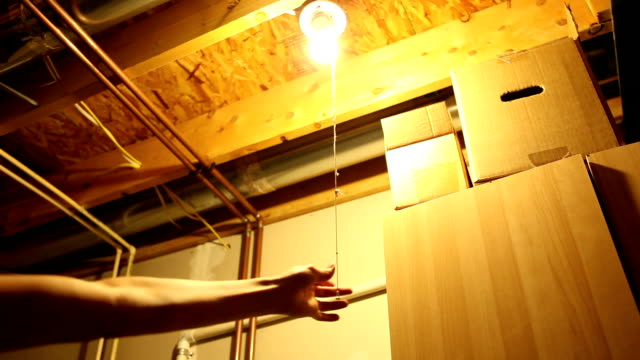hand pulls string turning light bulb off and on - basement stock videos & royalty-free footage