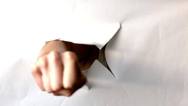 vídeos de stock e filmes b-roll de mão de puncionar através do livro branco - dar murros
