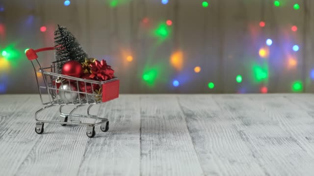 Hand push mini shopping cart with christmas tree and gifts on the background of led lamps garland.