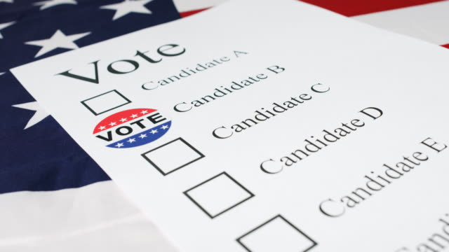 Hand put Voted sticker on ballot paper Man hand marks selected candidate with Voted sticker on a paper ballot for 2020 US Presidential Elections. president stock videos & royalty-free footage