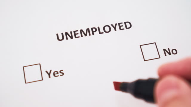 a hand puts a check mark next to yes on white paper under the word unemployed in the checklist - unemployment stock videos & royalty-free footage
