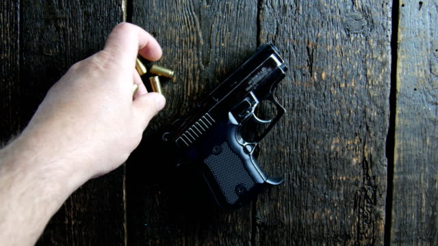 Hand puts ammo on wooden background