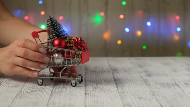 Hand puts mini shopping cart with christmas tree and gifts on the background of led lamps garland.
