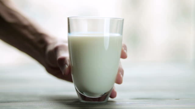 el ahşap masanın üzerine bir bardak süt koyar. - süt stok videoları ve detay görüntü çekimi