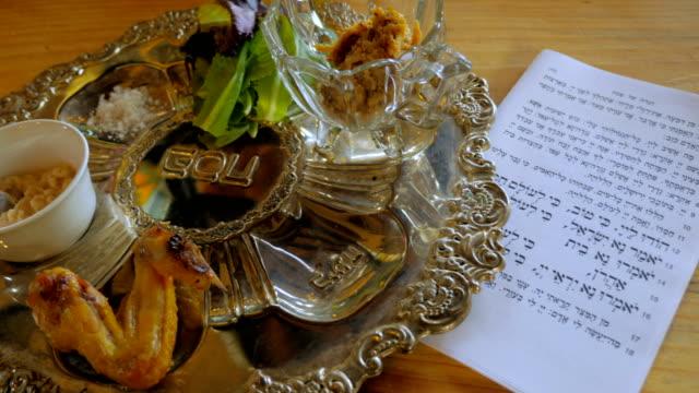 vídeos y material grabado en eventos de stock de una mano pone los toques finales en una placa de seder de pascua - dolly - pascua judía