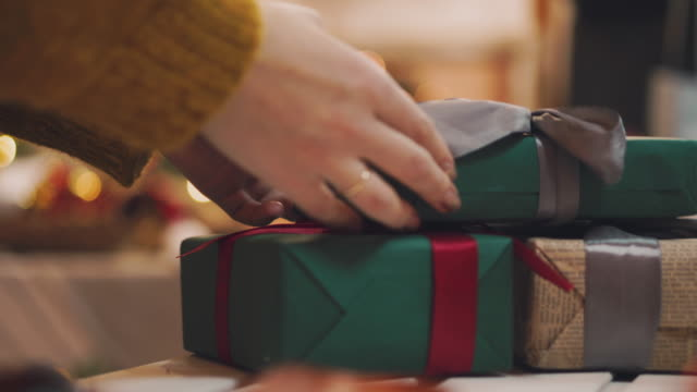 4k hand puts wrapped gift box under the christmas tree - decorazione natalizia video stock e b–roll