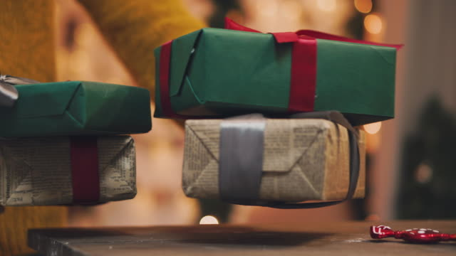 4k hand puts wrapped gift box under the christmas tree - sotto video stock e b–roll