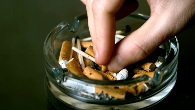 hand putting cigarette out in ashtray - släcka bildbanksvideor och videomaterial från bakom kulisserna