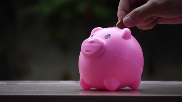 Hand putting coins in a pink piggy bank, saving money concept