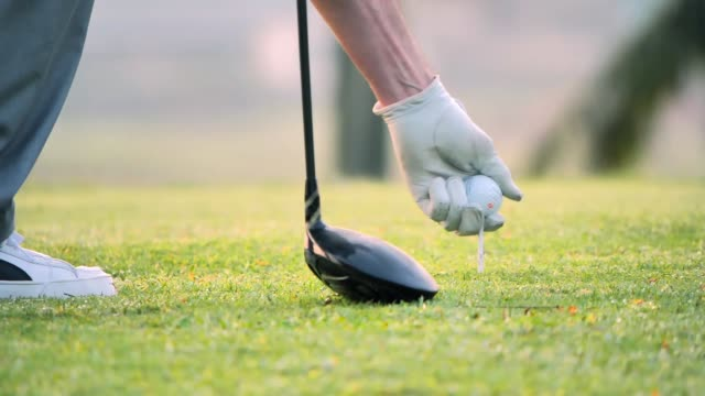Hand putting golf ball on tee in golf course.Sports Cinemagraphs