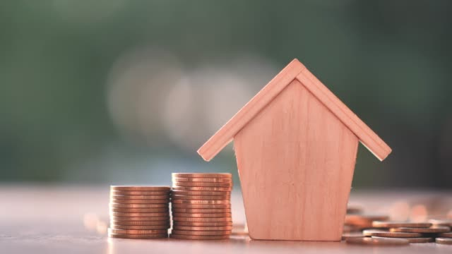 Hand putting money coins with home model on nature green background and sunlight. Finance and house loan, refinance, Property Investment and business, credit concept. Slow Motion