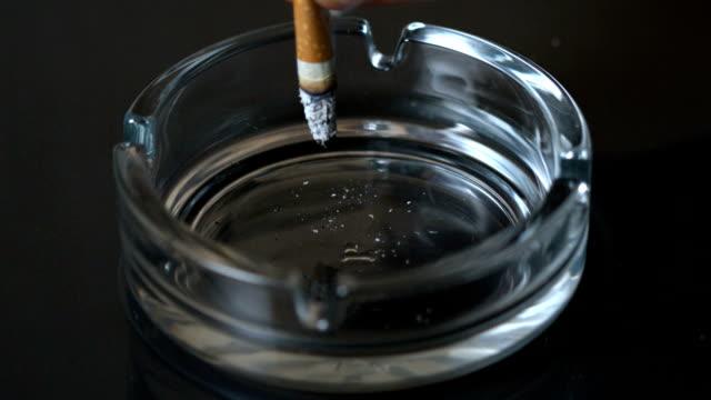 hand putting out a cigarette in empty ashtray - släcka bildbanksvideor och videomaterial från bakom kulisserna