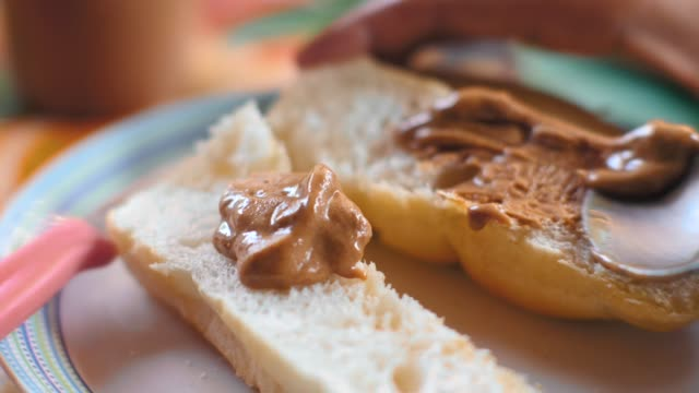 A hand putting peanut butter spread on a white bread using fork. Close up shot A hand putting peanut butter spread on a white bread using fork. Close up shot. A woman's hand spreading peanut butter on bread, delicious source of protein. satisfaction stock videos & royalty-free footage