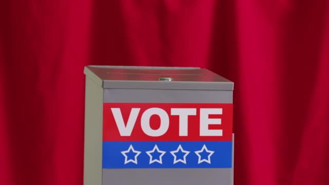 Hand putting vote into ballot box video