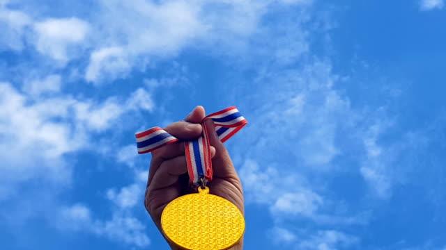 手を上げた、空に対して金目たるを保持します。賞と勝利の概念 - メダル点の映像素材/bロール