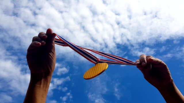 손, 하늘에 대 한 골드 메달을 들고입니다. 수상 및 승리 개념 - ribbon 스톡 비디오 및 b-롤 화면