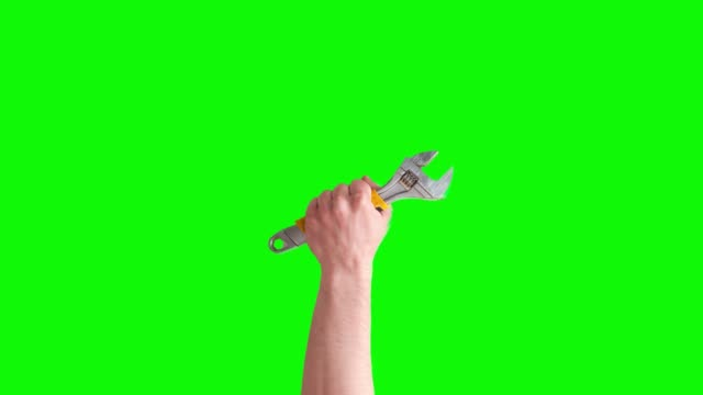 Hand raises adjustable wrench, tools isolated on green screen. Mechanic tools concept