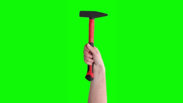 Hand raises red hammer, tools isolated on green screen. Mechanic tools concept