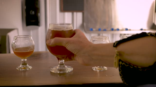hand reaches in to pickup a snifter of robust craft beer and puts it back - jumping filmów i materiałów b-roll