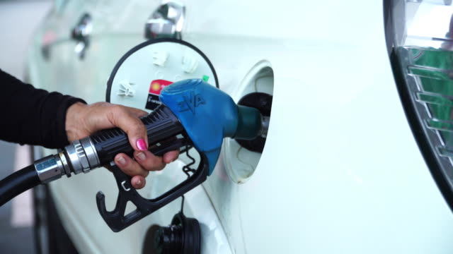 Hand refueling the car with fuel Close-up of female's hand refueling the car with fuel at gas station handle stock videos & royalty-free footage