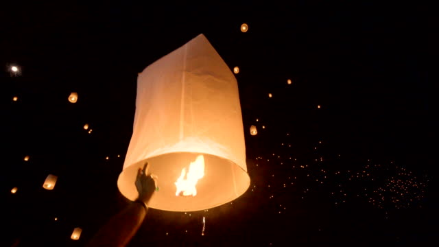 hand releasing hot air paper lantern up to the sky in yi peng festival, chiang mai, thailand. - spostarsi verso l'alto video stock e b–roll