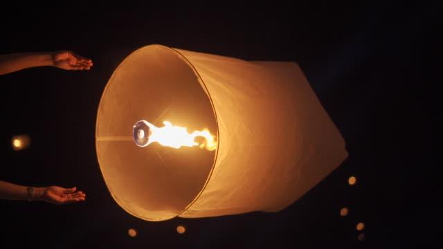 slo mo hand releasing lantern to the sky in yee peng festival (yi peng) - китайский фонарь стоковые видео и кадры b-roll