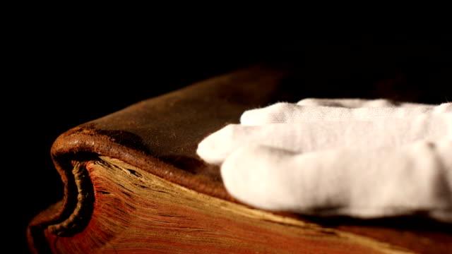 hand tar bort damm från den gamla boken close up - påve bildbanksvideor och videomaterial från bakom kulisserna