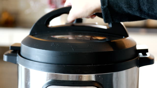 Hand Removing Pressure Cooker Lid Hand removing pressure cooker lid. cooking pan stock videos & royalty-free footage