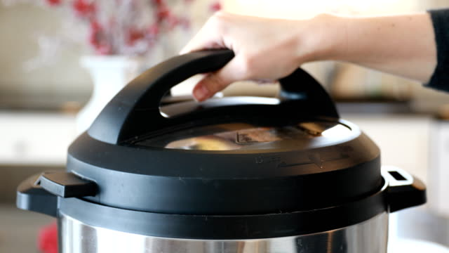 Hand Removing Pressure Cooker Lid with Steam Hand removing pressure cooker lid with steam. cooking pan stock videos & royalty-free footage