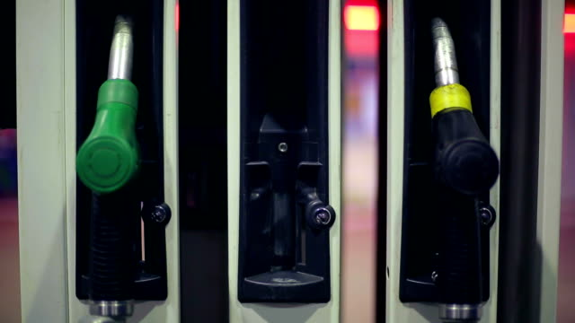 Hand returns a fuel nozzles at a gas station video