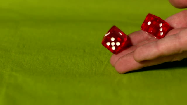 Hand rolling two red dice on green table video