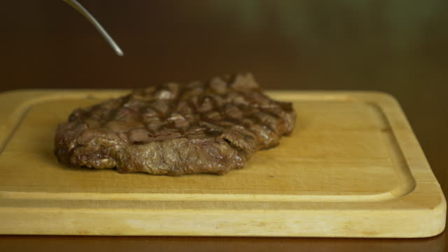 Hand salt steak. The salt slowly falls on top of the meat. The meat lies on a wooden board. video
