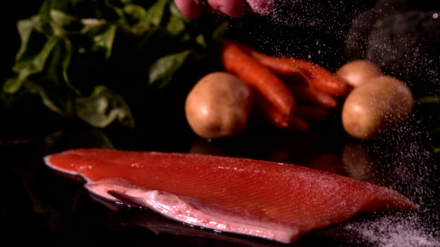 Hand seasoning trout fillet in front of vegetable selection video