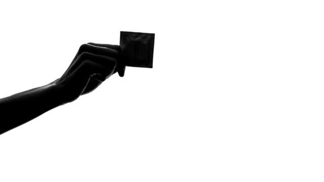 Hand shadow holding condom, responsible attitude, health care, contraception video
